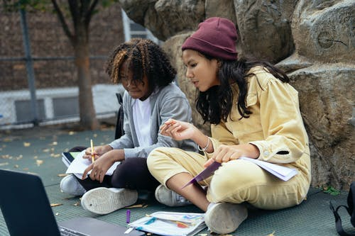 Multiracial schoolchildren with workbooks interacting while watching netbook and sitting with crossed legs on street
