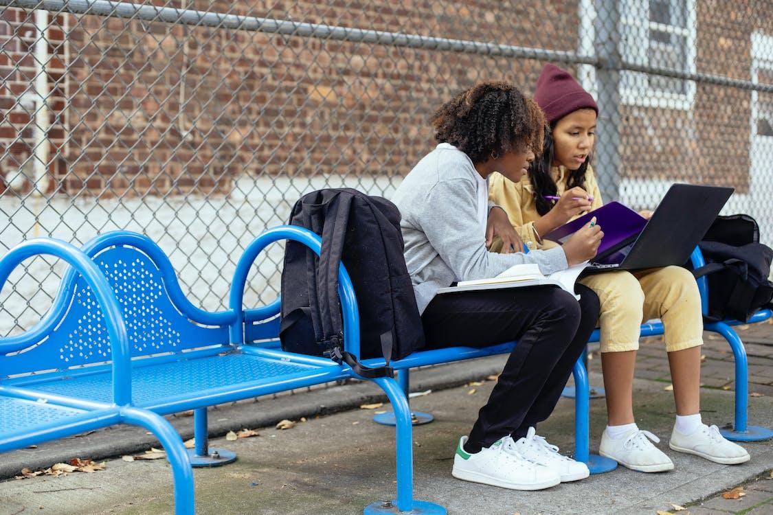 Focused multiethnic schoolchildren with laptop studying on urban bench