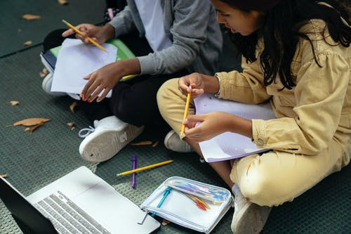 From above of crop multiethnic schoolchildren with copybook speaking while sitting with crossed legs near laptop on pavement