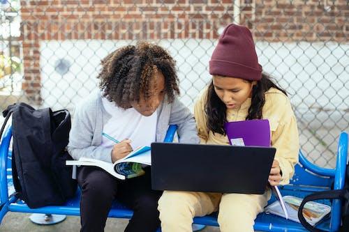 Attentive multiracial schoolchildren with laptop doing homework on street bench