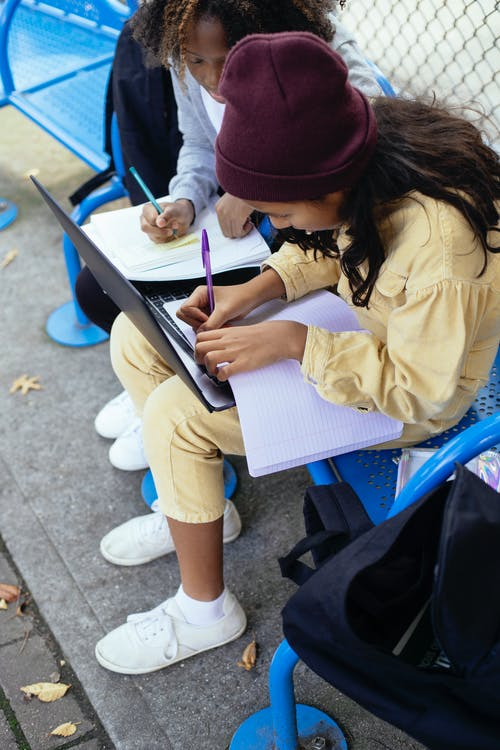High angle of crop anonymous multiracial schoolkids with netbook writing in workbook while doing homework on urban bench