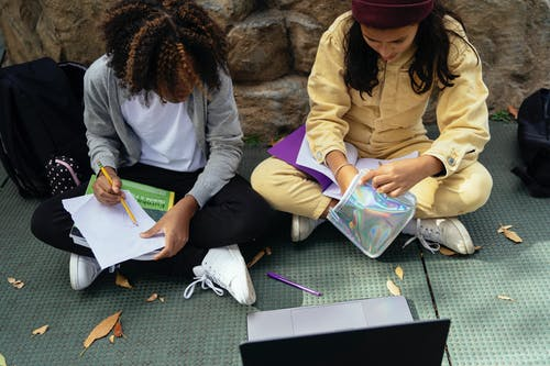 Crop diverse schoolchildren doing homework on pavement near laptop