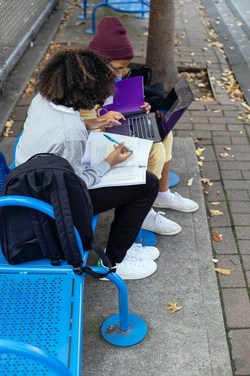 Anonymous multiethnic schoolchildren with laptop and copybooks studying on bench