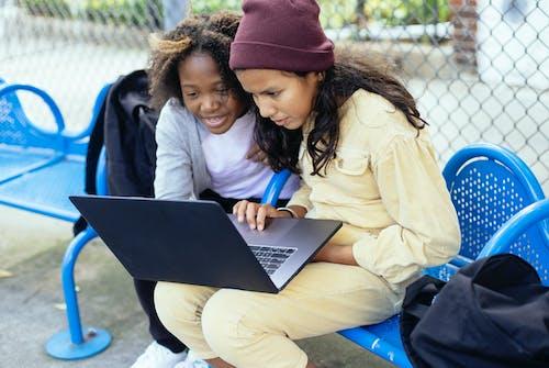 Crop multiethnic schoolchildren watching laptop on urban bench