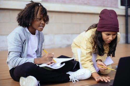 Attentive multiracial schoolchildren surfing internet on laptop while doing homework