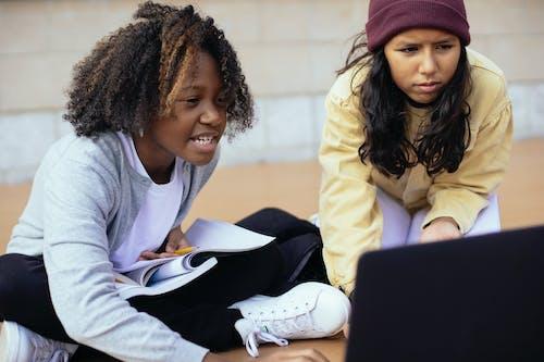 Crop attentive diverse schoolchildren watching laptop while studying on street