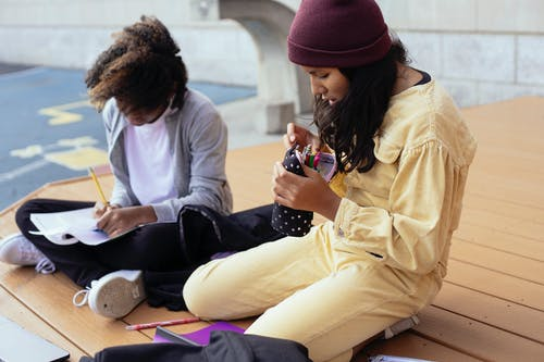 Crop Hispanic schoolgirl with pencil case sitting near anonymous black girlfriend writing in copybook while doing homework on wooden platform