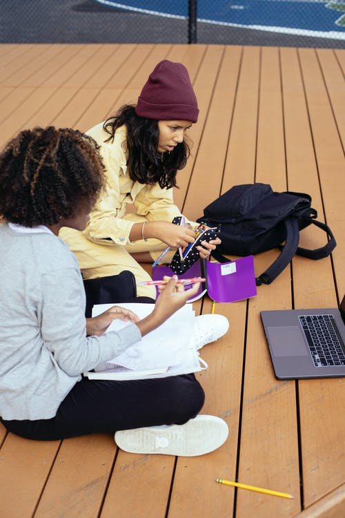 From above side view of anonymous focused multiracial schoolchildren watching netbook while sitting with copybooks and doing homework on street