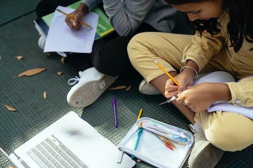 Crop Hispanic schoolgirl writing in copybook near unrecognizable friend outdoors