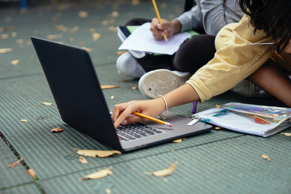 Faceless diverse schoolchildren typing on laptop while studying on street
