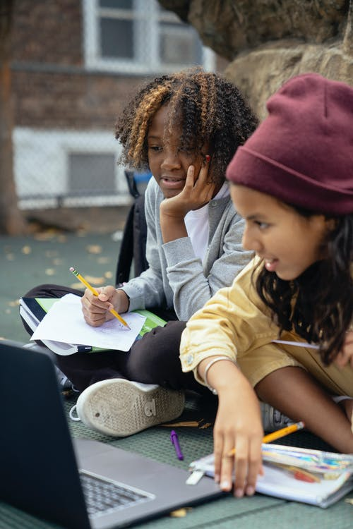 Crop glad multiethnic schoolkids sitting with crossed legs while watching netbook and doing homework on urban pavement