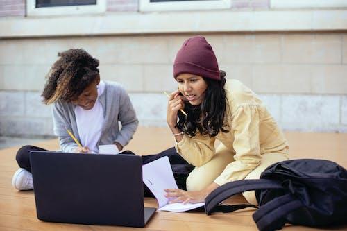 Attentive Hispanic schoolchild touching face while watching laptop near smiling black girlfriend studying on wooden platform