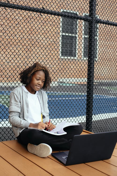 Full body of African American child in casual clothes sitting with crossed legs with laptop and notepad while doing homework