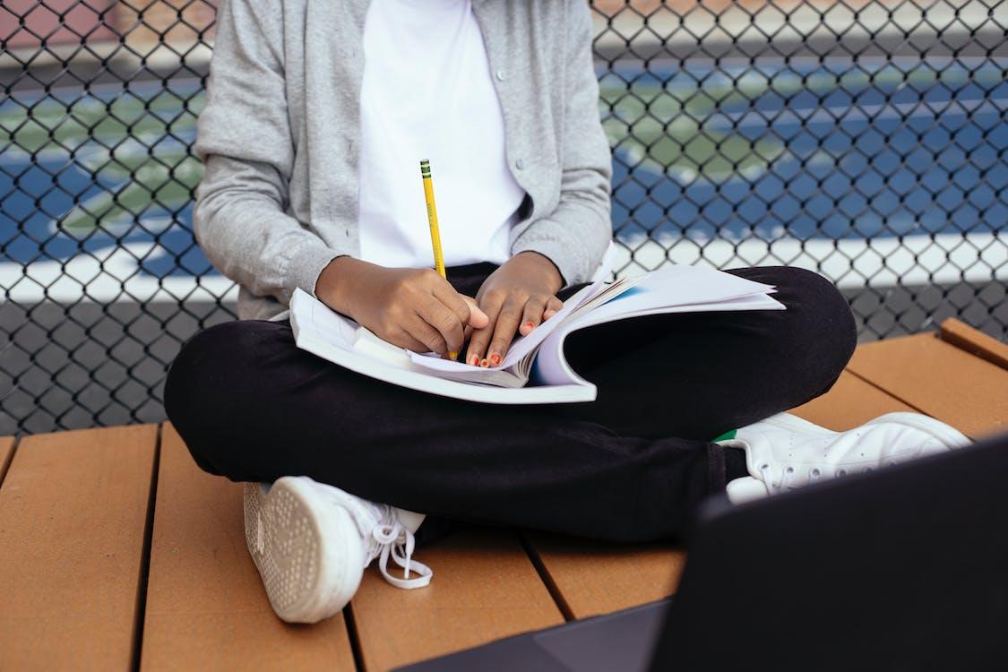 Crop ethnic pupil doing homework in schoolyard