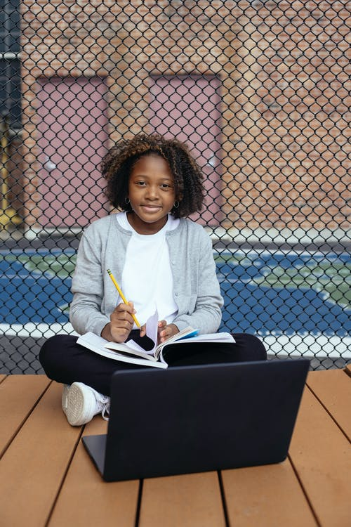 Happy African American schoolgirl sitting on wooden surface with laptop and notepad while preparing for exam and looking at camera