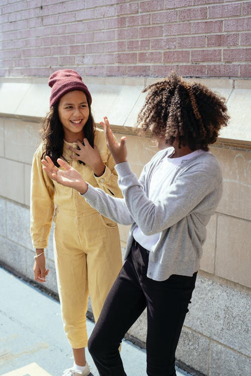 Cheerful multiracial schoolgirls in casual clothes standing near brick building and smiling while discussing news