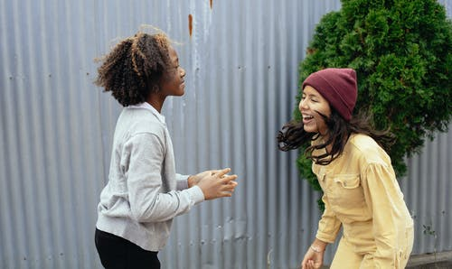 Side view of multiracial girls smiling while having fun together in backyard of house