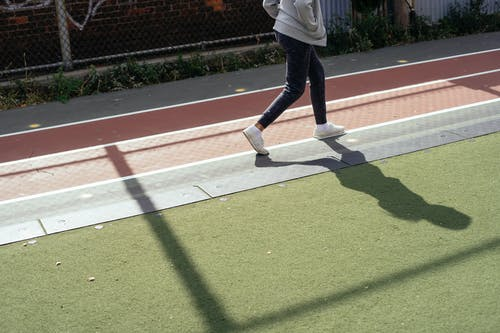 Crop faceless kid in sportswear holding hands in pockets while walking and preparing for sprint on sports ground