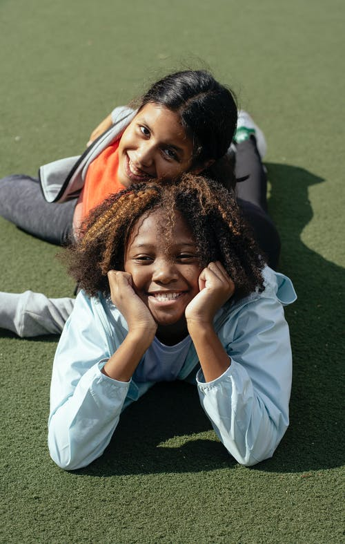 Alunas Multiétnicas Felizes Relaxando No Campo De Esportes