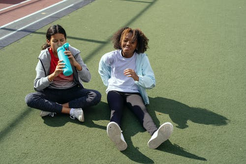 Full body of diverse girlfriends in sportswear sitting on lawn while drinking water after workout together