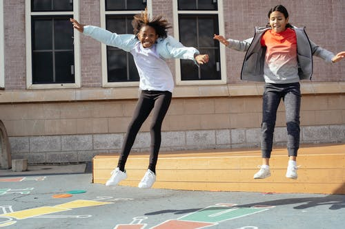 Full body of happy multiracial girls jumping off wooden scene onto playground while spending free time after lessons on backyard of school on sunny day