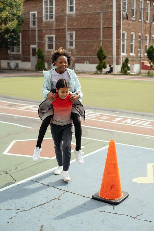 Menina Ativa Pegando Carona Em Um Colega De Classe E Correndo Ao Redor Do Cone Vermelho No Playground