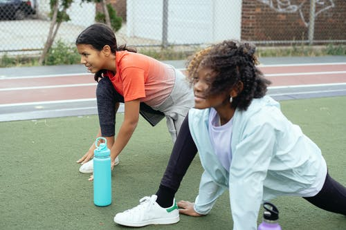 Side view of smiling multiracial sportive kids wearing activewear warming up legs before running training on outdoors track in daytime