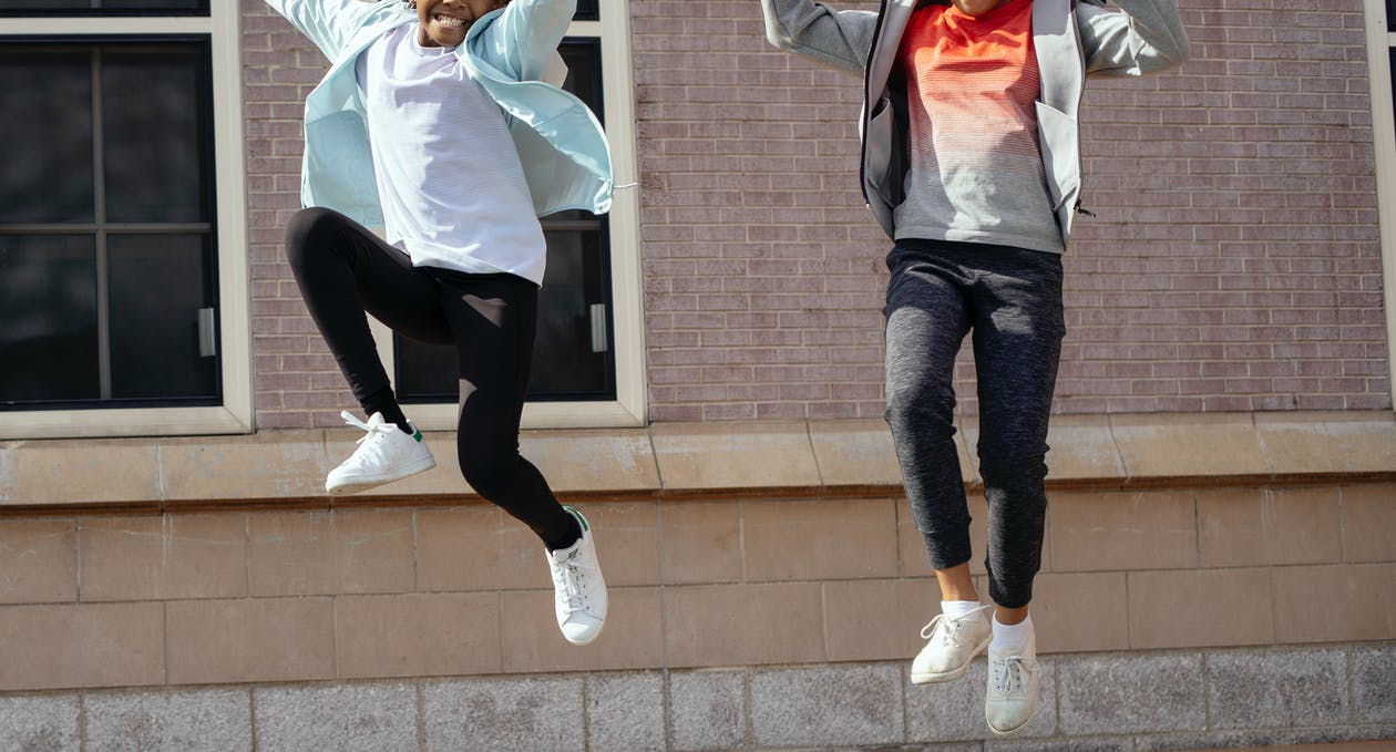 Crop smiling black girl and unrecognizable classmate wearing sportive clothes jumping high together while spending free time after lessons near school