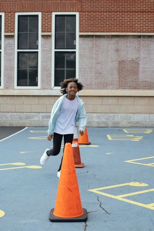 Happy black girl running around red cones on playground near school
