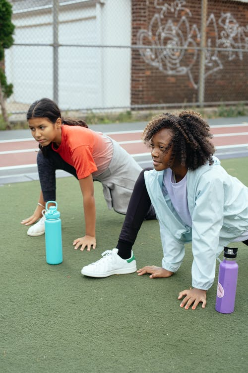 Multiracial girls stretching on sports ground