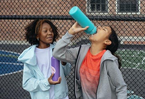Tired diverse schoolgirls drinking water
