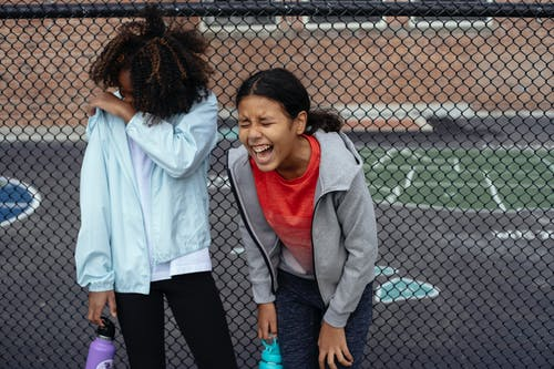Multiethnic schoolgirls laughing on sports ground
