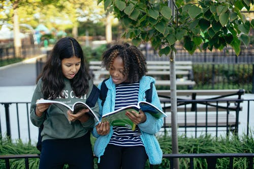 Concentrated multiracial girls in casual outfits reading notes in copybooks leaning on metal fence