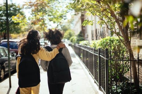 Back view of unrecognizable girls walking together along street while returning home from school