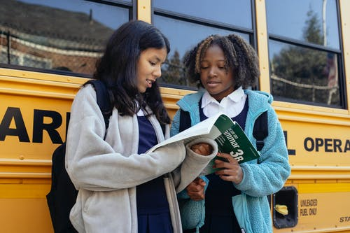 Schoolgirls with textbook near bus