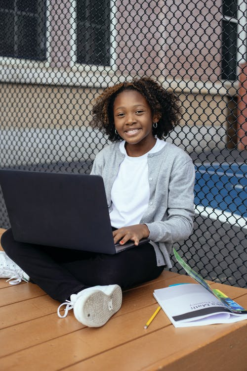 Black student with laptop and textbook