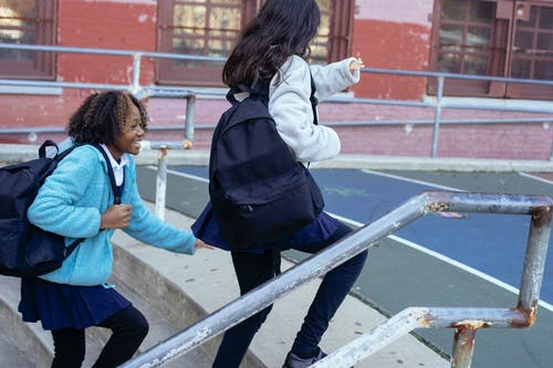 Cheerful girl hurrying to school
