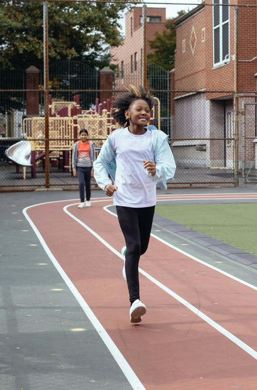 Full body of African American girl in sportswear running on track during training on sports ground