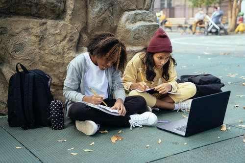 Full body of focused multiracial girls in casual wear with laptop and copybooks sitting on ground and doing homework together