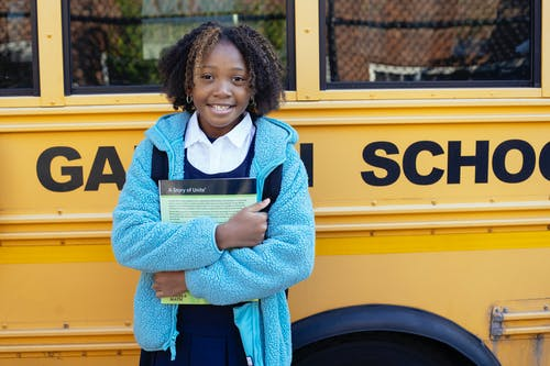 Cheerful African American girl in school uniform and warm jacket standing with textbook near yellow school bus and looking at camera