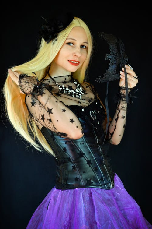 Positive female wearing witchcraft costume and wig standing with masquerade mask in studio and looking at camera