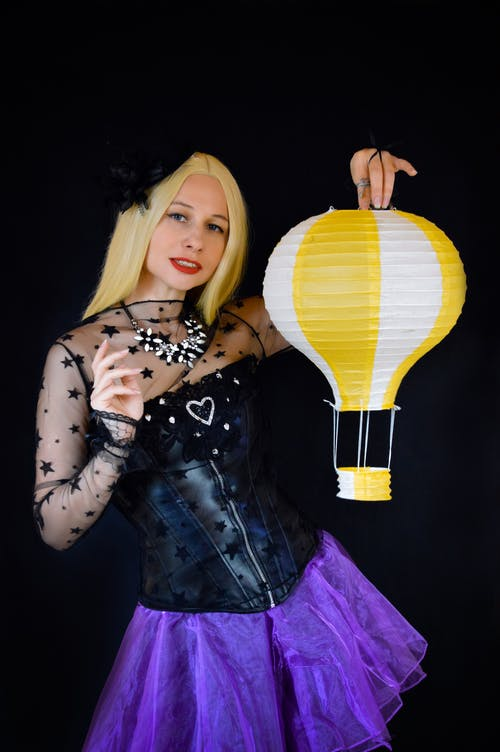 Female model wearing black corset and skirt for Halloween standing with paper lantern and looking at camera