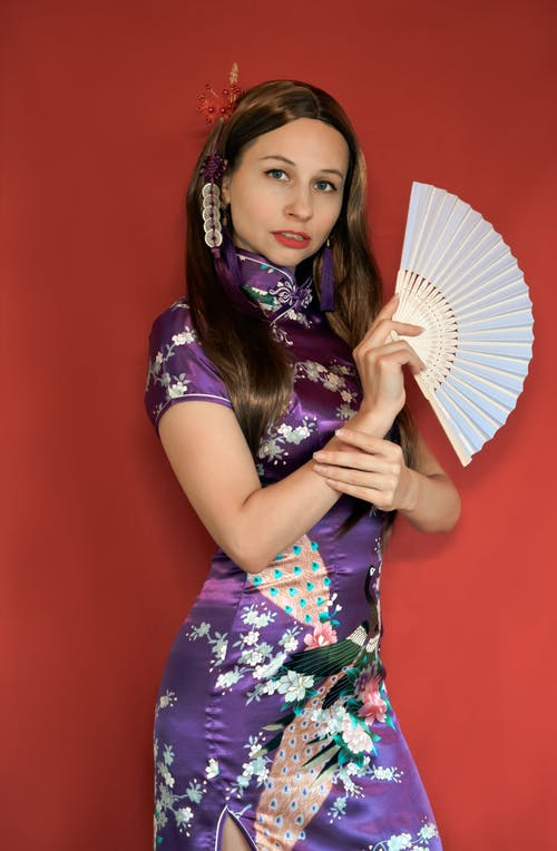 Stylish woman with fan standing in studio