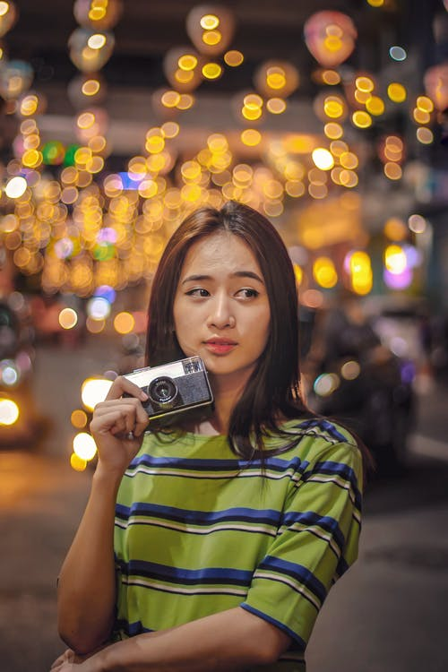 Young Asian woman with vintage photo camera