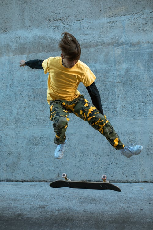 Boy in Yellow Shirt and Black Pants Jumping on Black Skateboard