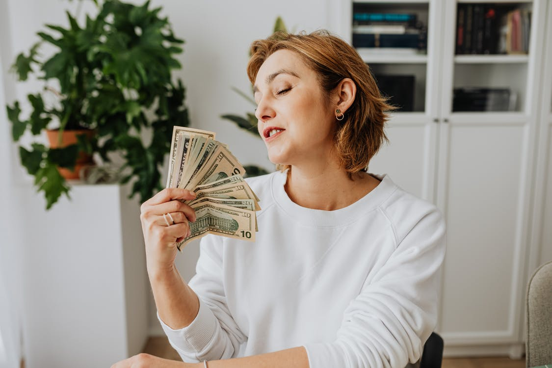 Woman Wearing a White Sweater Holding Money
