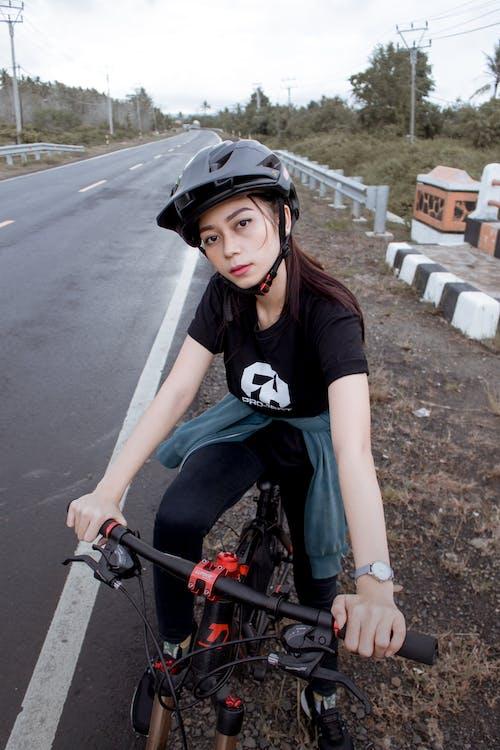 Woman in Black T-shirt Riding a Mountain Bike