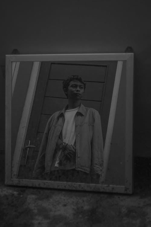 Black and white of serious young Asian male in trendy outfit standing in front of mirror near door and looking away