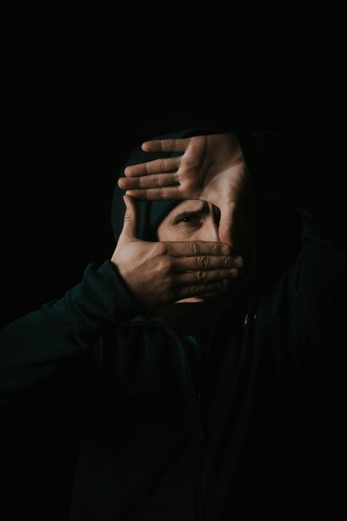Man in Black Leather Jacket Covering His Face