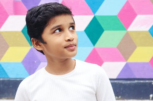Ethnic child in casual clothes standing near wall with colorful graffiti and smiling while looking up
